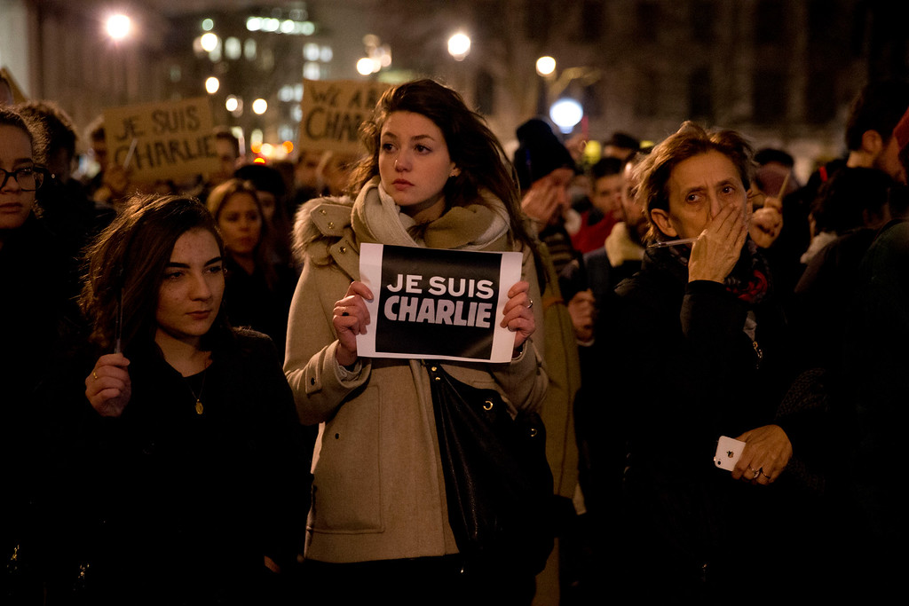 . People hold up pens and posters reading \'I am Charlie\' in French as they take part in a vigil of people, including many who were French, to show solidarity with those killed in an attack at the Paris offices of weekly newspaper Charlie Hebdo, in Trafalgar Square, London, Wednesday, Jan. 7, 2015. Masked gunmen stormed the Paris offices of a weekly newspaper that caricatured the Prophet Muhammad, methodically killing 12 people Wednesday, including the editor, before escaping in a car. It was France\'s deadliest postwar terrorist attack.  (AP Photo/Matt Dunham)