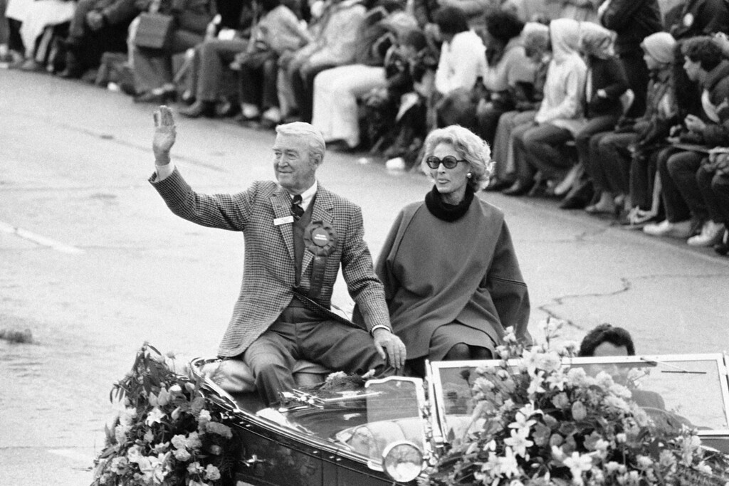 . Actor Jimmy Stewart, grand marshal of the 93rd Tournament of Roses Parade, waves to the crowd as he\'s accompanied by his wife, Gloria, during the parade in Pasadena, Calif., Jan. 1, 1982. (AP Photo/Reed Saxon)