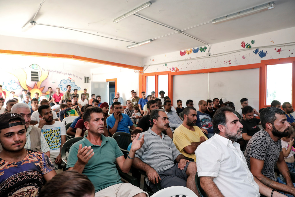 . Migrants watch on a TV set the final soccer match between Croatia and France during the 2018 soccer World Cup in Russia, at Ritsona camp, northeast of Athens, Sunday, July 15, 2018. (AP Photo/Yorgos Karahalis)