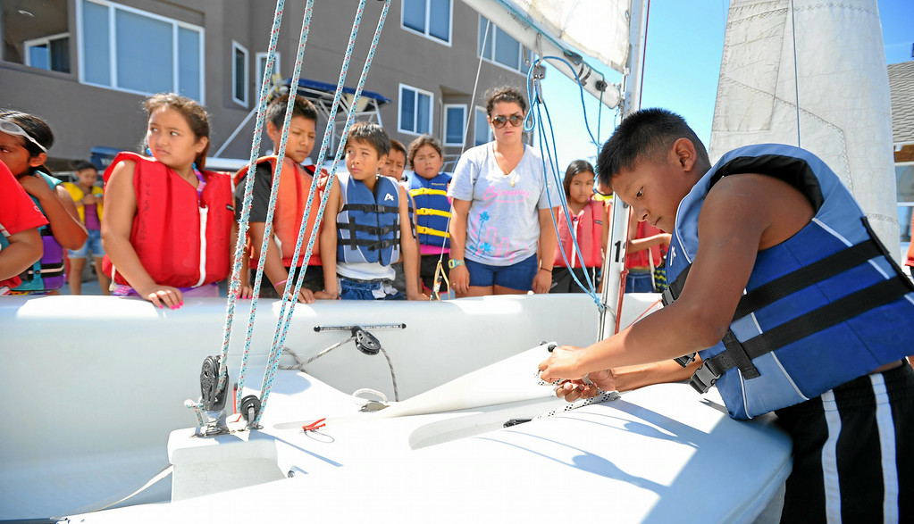 . A group of Huntington Beach school children from the El Viento Foundation\'s Reach program watch as another ties off a rope as they learn to sail in Long Beach, CA on Wednesday, July 30, 2014. The students, who come from a lower income neighborhood, were given the sailing lessons by staff at the U.S. Sailing Center. (Photo by Scott Varley, Daily Breeze)