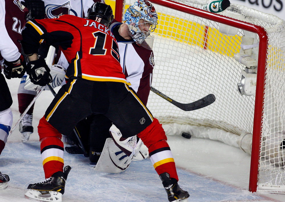 . Colorado Avalanche goalie Semyon Varlamov, right, of Russia, looks back at the puck in the net as Calgary Flames\' Tim Jackman watches during the first period of their NHL hockey game in Calgary, Alberta, Wednesday, March 27, 2013. (AP Photo/The Canadian Press, Jeff McIntosh)