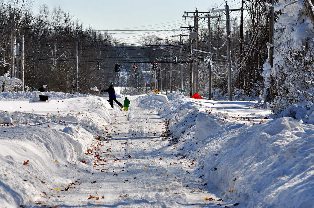 . Residents try to shovel  through nearly five feet of snow on November 19, 2014 in the Lakeview neighborhood of Buffalo, New York. The record setting Lake effect snowstorm dumped up to six feet of snow in less than 24 hours closing a one hundred mile section of The New York State Thruway as well as other major roads around Buffalo. Four deaths have already been  attributed to the storm and a second round beginning late Wednesday evening will bring up to three more feet of snow overnight. (Photo by John Normile/Getty Images)