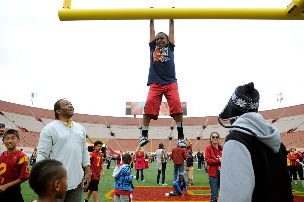 . Jeremy Raymore hangs from the goalpost following USC\'s Spring Football Game. (Michael Owen Baker/Staff Photographer)