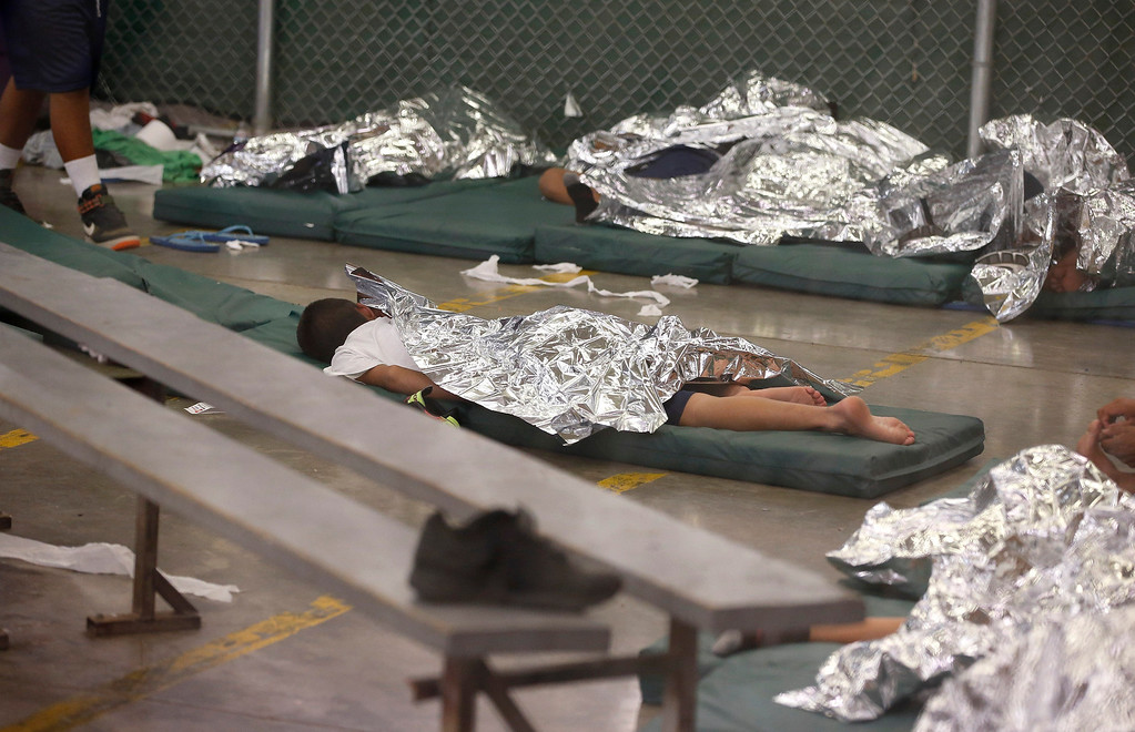 . Young boys sleep in a holding cell where hundreds of mostly Central American immigrant children are being processed and held at the U.S. Customs and Border Protection Nogales Placement Center on Wednesday, June 18, 2014, in Nogales, Ariz.   (AP Photo/Ross D. Franklin, Pool)