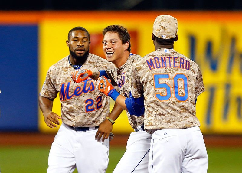 . Wilmer Flores #4 of the New York Mets celebrates his ninth inning game winning sacrifice fly against the Colorado Rockies with teammates Rafael Montero #50 and Eric Young Jr. #22 at Citi Field on September 8, 2014 in the Flushing neighborhood of the Queens borough of New York City.  (Photo by Jim McIsaac/Getty Images)