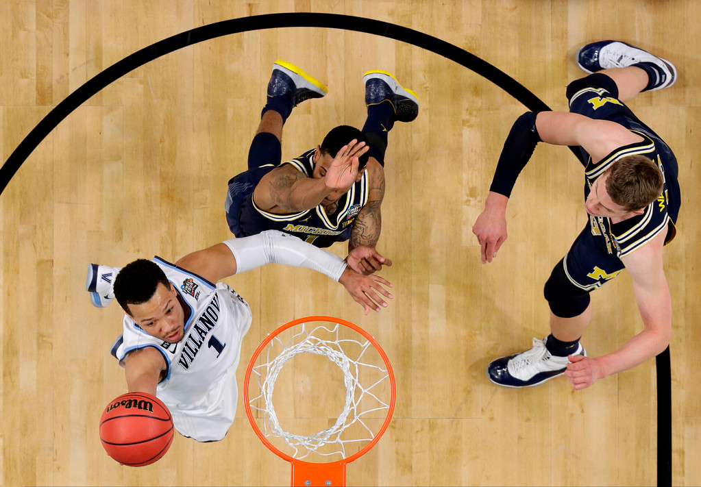 . Villanova guard Jalen Brunson, left, drives to the basket over Michigan defenders Charles Matthews, center, and Moritz Wagner, right, during the first half in the championship game of the Final Four NCAA college basketball tournament, Monday, April 2, 2018, in San Antonio. (AP Photo/Eric Gay)