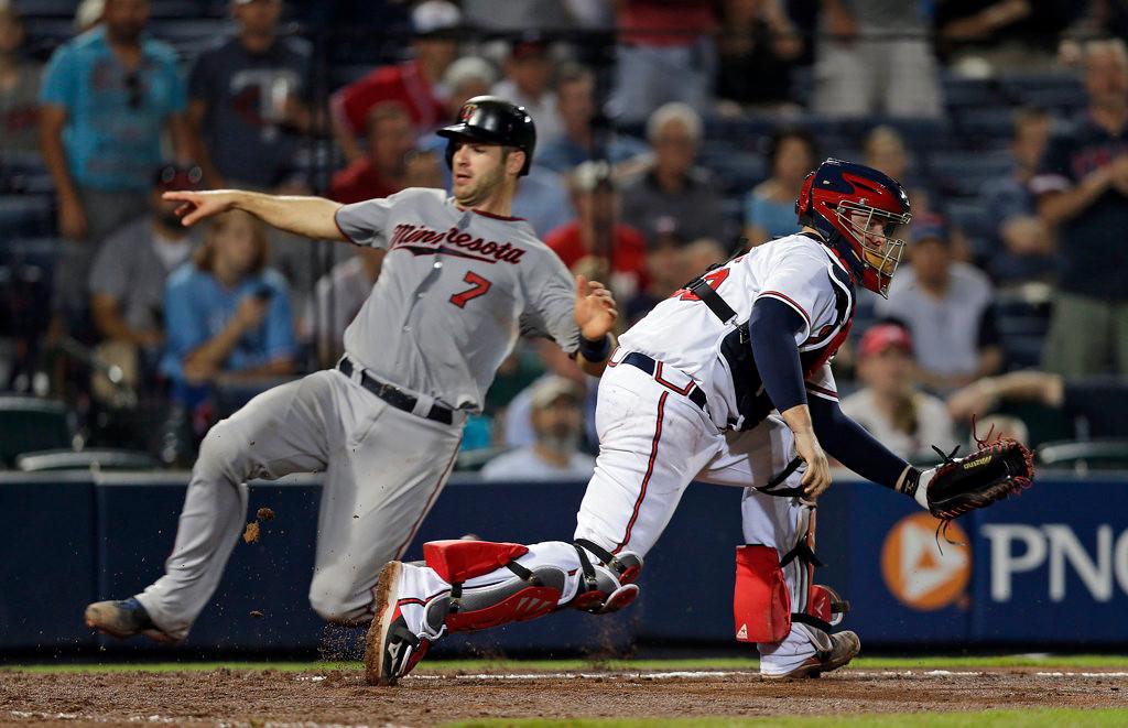. Minnesota Twins\' Joe Mauer scores as Atlanta Braves catcher Brian McCann handles the late throw in the eighth inning. (AP Photo/John Bazemore)