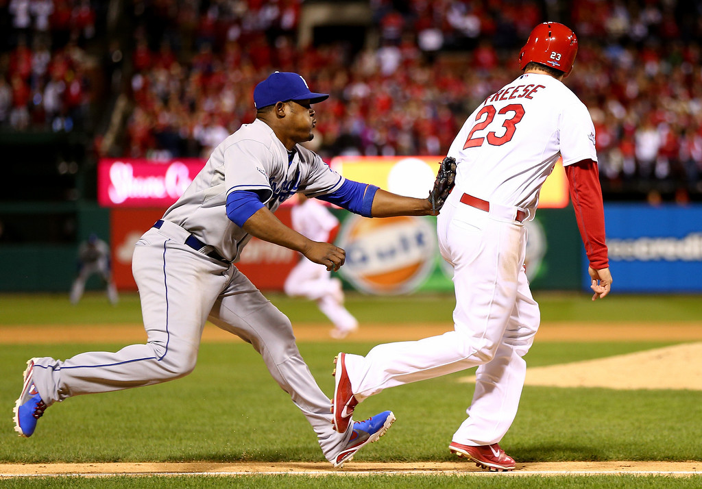 . ST LOUIS, MO - OCTOBER 18:  Juan Uribe #5 of the Los Angeles Dodgers tags out David Freese #23 of the St. Louis Cardinals on a run down in the fifth inning in Game Six of the National League Championship Series at Busch Stadium on October 18, 2013 in St Louis, Missouri.  (Photo by Elsa/Getty Images)