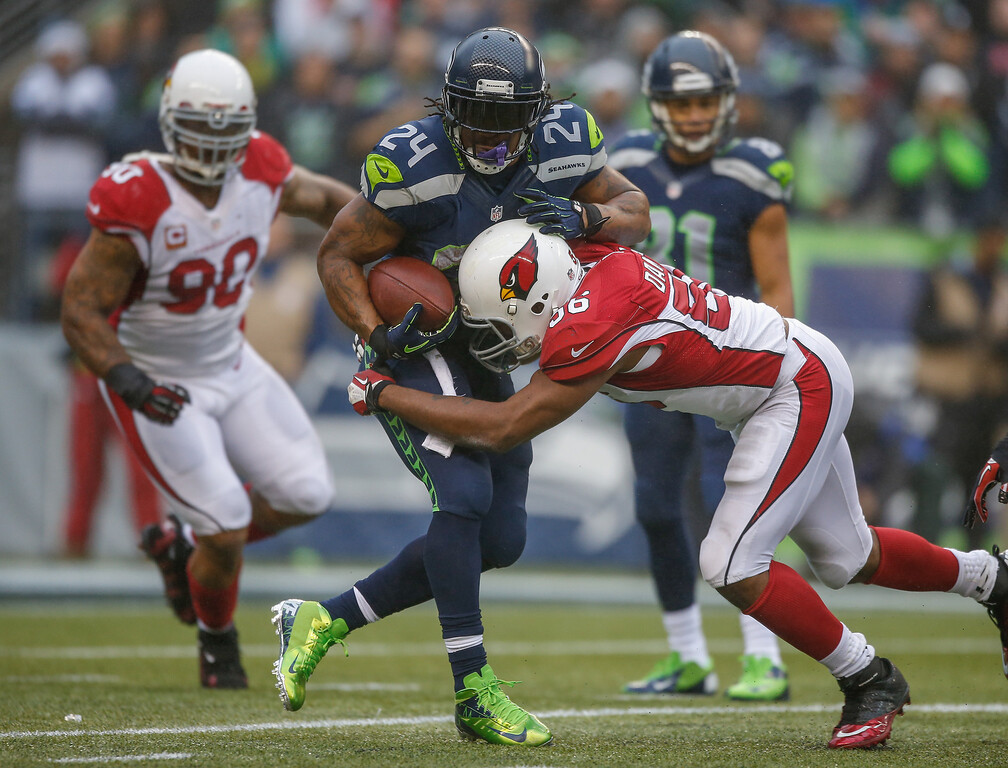 . Running back Marshawn Lynch #24 of the Seattle Seahawks rushes against linebacker Karlos Dansby #56 of the Arizona Cardinals at CenturyLink Field on December 22, 2013 in Seattle, Washington.  (Photo by Otto Greule Jr/Getty Images)