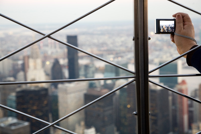 A visitor taking a picture of NYC from the top of the Empire State Building