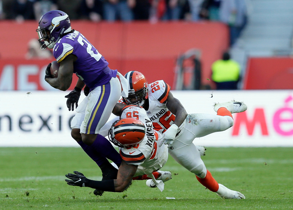 . Minnesota Vikings running back Jerick McKinnon, left, runs with the ball as Cleveland Browns linebacker Christian Kirksey (58) and safety Derrick Kindred (26) defend during the first half of an NFL football game at Twickenham Stadium in London, Sunday Oct. 29, 2017. (AP Photo/Tim Ireland)