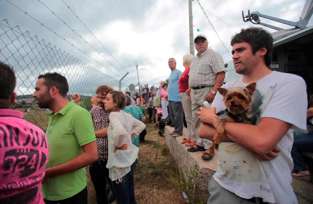 . Onlookers view the wreckage of a train crash near Santiago de Compostela, northwestern Spain, July 25, 2013.  REUTERS/Miguel Vidal