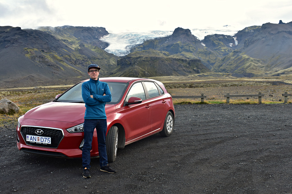 Red Hyundai I30 Rental Car In Iceland with man in front