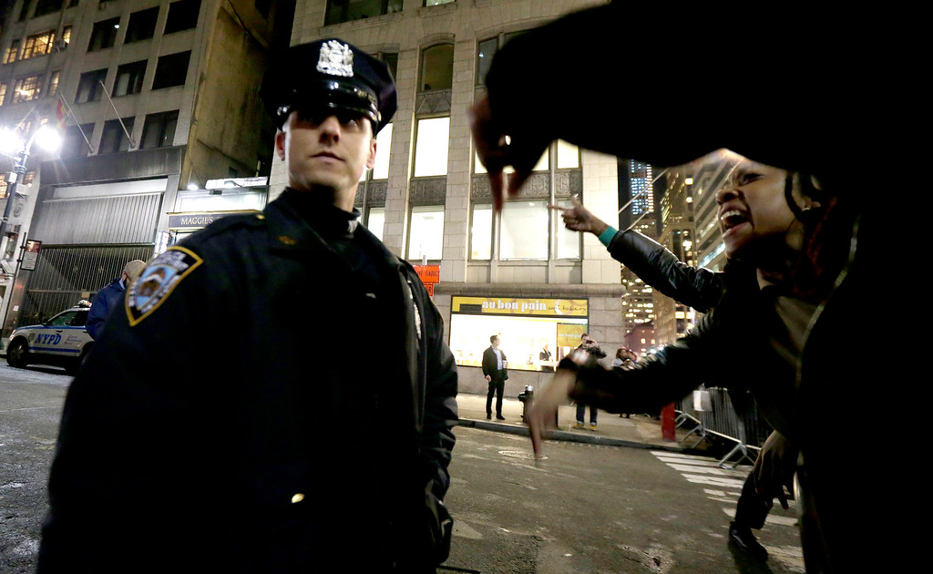 . A woman, right, yells at a New York City Police officer during a protest after it was announced that the police officer involved in the death of Eric Garner is not being indicted, Wednesday, Dec. 3, 2014, in New York. A grand jury cleared the white New York City police officer Wednesday in the videotaped chokehold death of Garner, an unarmed black man, who had been stopped on suspicion of selling loose, untaxed cigarettes, a lawyer for the victim\'s family said. A video shot by an onlooker and widely viewed on the Internet showed the 43-year-old Garner telling a group of police officers to leave him alone as they tried to arrest him. The city medical examiner ruled Garner\'s death a homicide and found that a chokehold contributed to it. (AP Photo/Julio Cortez)