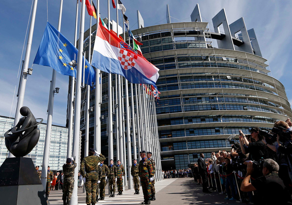 . Soldiers of the Eurocorps hoist the flag of Croatia in front of the European Parliament in Strasbourg, July 1, 2013. Two decades since fighting itself free of Yugoslavia, Croatia becomes the 28th member of the European Union on Monday against a backdrop of economic woes in the Adriatic republic and the bloc it is joining. REUTERS/Vincent Kessler