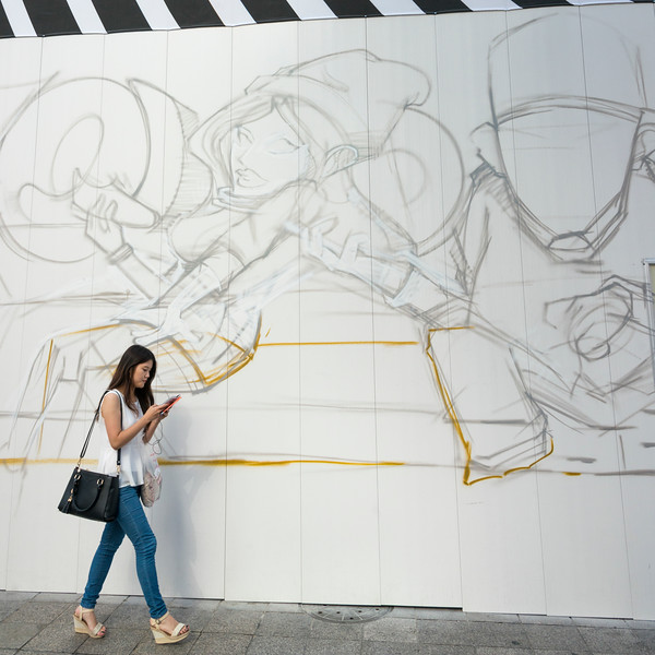 Woman walking in front of graffiti covered wall and using mobile phone, Gangnam District, Seoul, South Korea