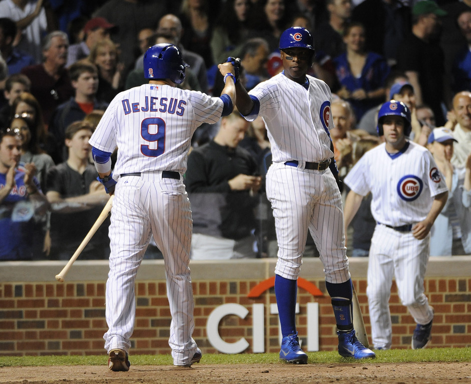 . David DeJesus #9 of the Chicago Cubs is greeted by Alfonso Soriano #12  after scoring against the Colorado Rockies during the seventh inning on May 15, 2013 at Wrigley Field in Chicago, Illinois.   (Photo by David Banks/Getty Images)