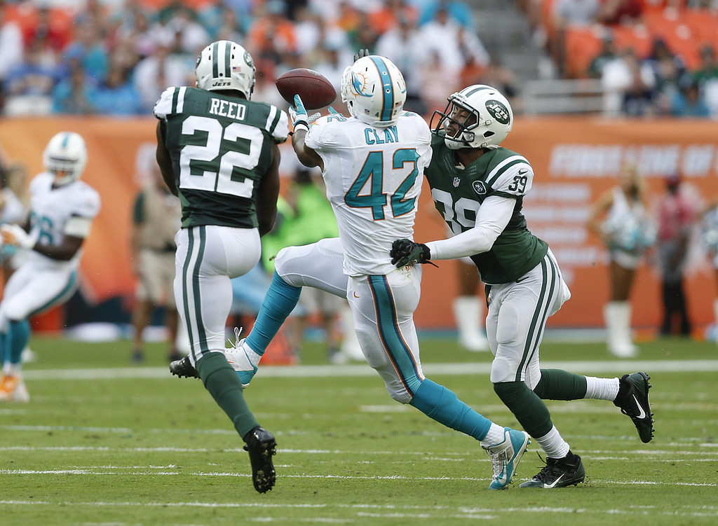 . Charles Clay #42 of the Miami Dolphins is unable to catch the ball while being defended by Aaron Berry #22 and Antonio Allen #39 of the New York Jets on December 29, 2013 at Sun Life Stadium in Miami Gardens, Florida. (Photo by Joel Auerbach/Getty Images)