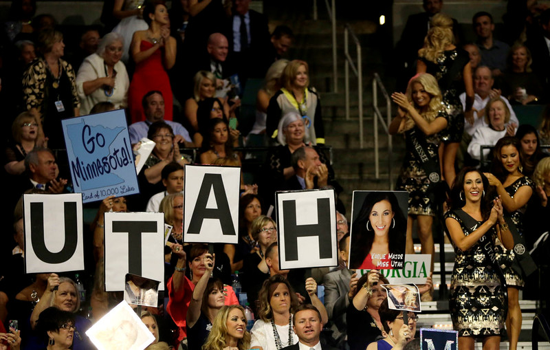 . Miss Utah Karlie Major, bottom right, stands with other contestants as supporters hold up signs during the Miss America 2015 pageant, Sunday, Sept. 14, 2014, in Atlantic City, N.J. (AP Photo/Julio Cortez)