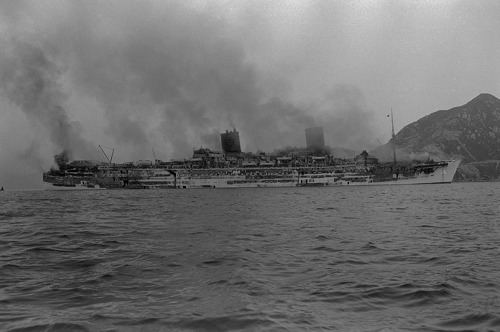 Description of . The former Queen Elizabeth remains afloat on January 10th, with its sleek hull and all 11 decks ravaged by a disastrous fire which roared through the ocean giant's once luxurious staterooms and salons. (Copyright Bettmann/Corbis / AP Images)