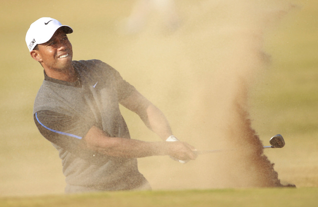 . Tiger Woods of the United States plays out of  a bunker onto the 14th green during the third round of the British Open Golf Championship at Muirfield, Scotland, Saturday July 20, 2013. (AP Photo/Peter Morrison)