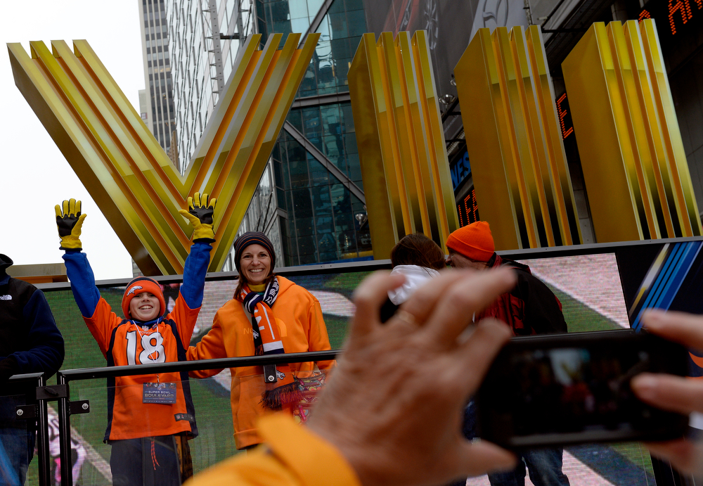 """. Broncos fans Lee Carey, of Long Branch, NJ, and her son Ryan, 12, have their photo made while visiting Times Square in New York, NY January 31, 2014. The NFL has transformed 13 blocks of Broadway into Super Bowl Boulevard before Sundays Super Bowl between the Denver Broncos and Seattle Seahawks. Ryan Predicted, \""""Broncos are gonna win but it will be very close, 23-20. Broncos in overtime.\"""" (Photo By Craig F. Walker / The Denver Post)"""