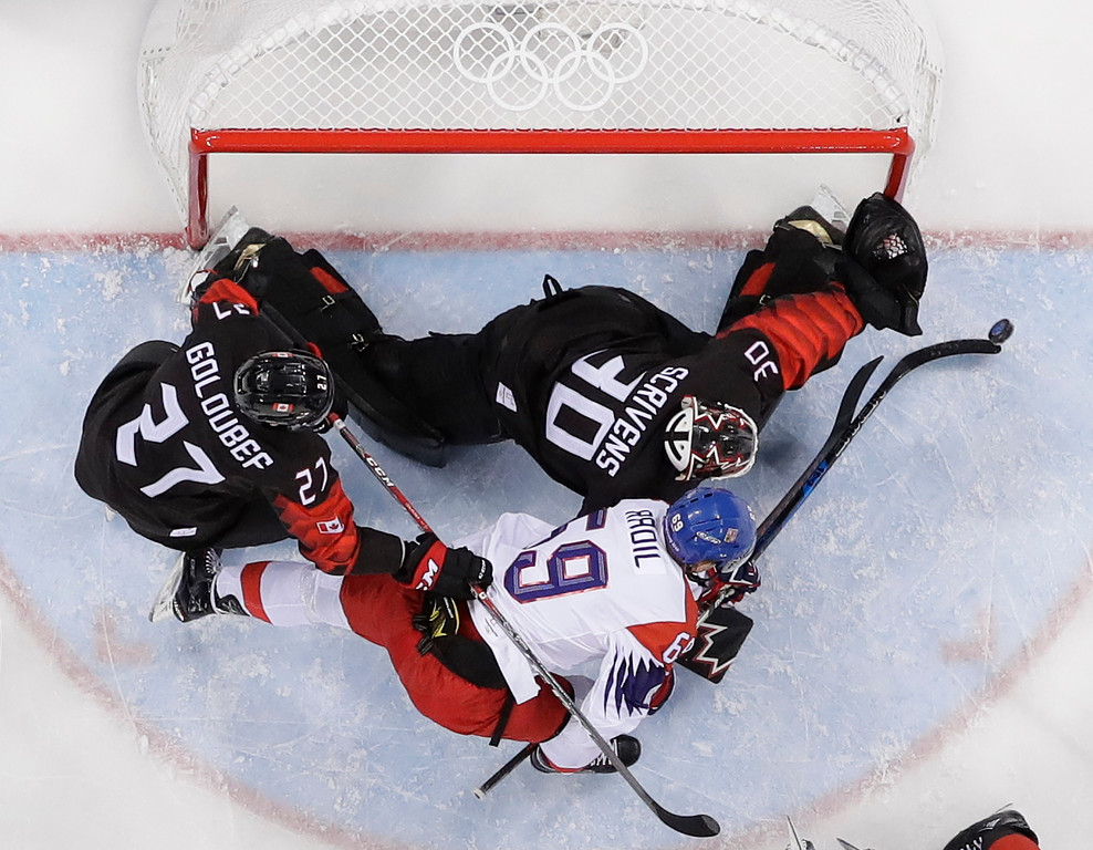 . Ben Scrivens (30), of Canada, and Lukas Radil (69), of the Czech Republic, battle for the puck during the first period of the preliminary round of the men\'s hockey game at the 2018 Winter Olympics in Gangneung, South Korea, Saturday, Feb. 17, 2018. (AP Photo/Julio Cortez)