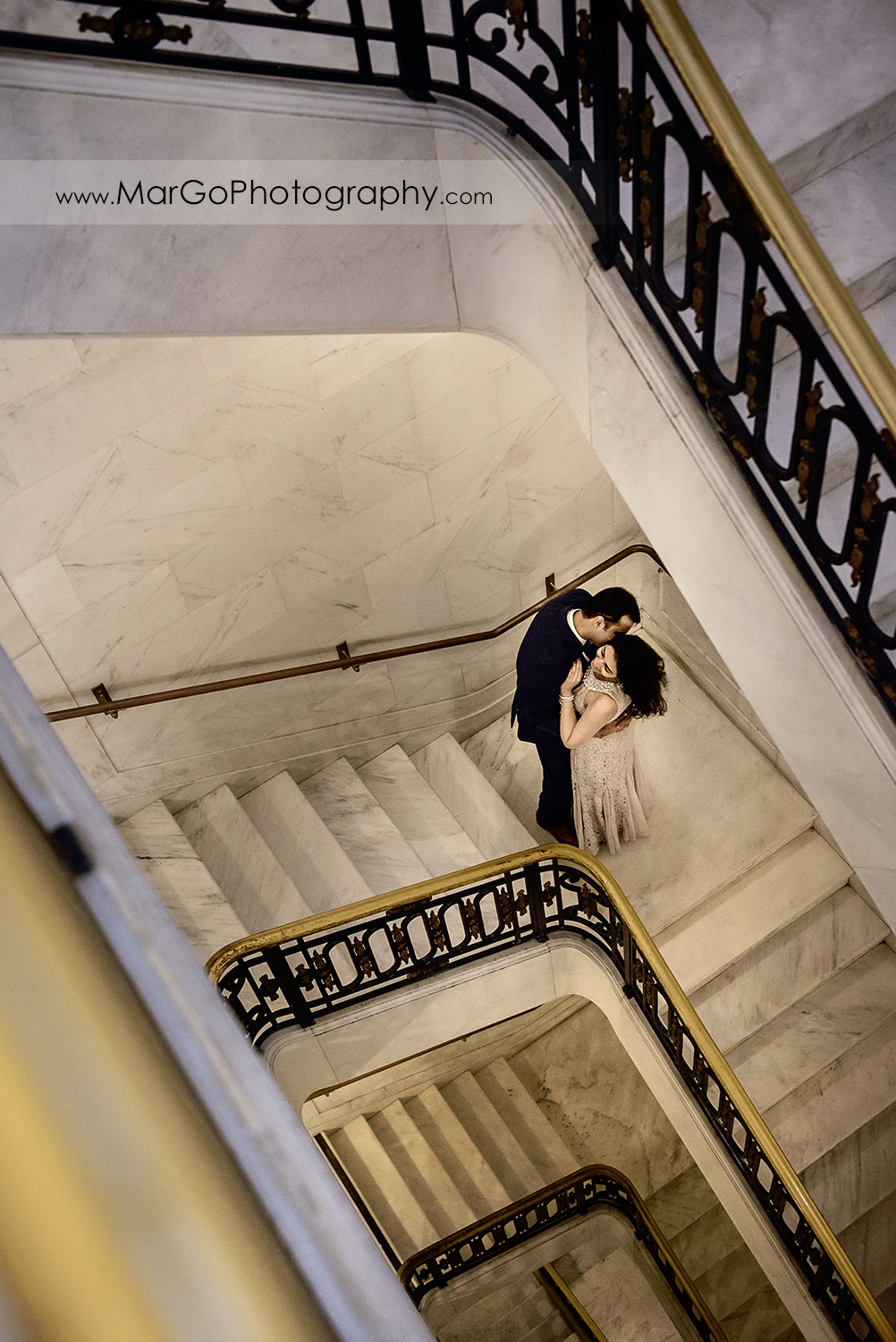 man in suit kissing woman in long dress on the stairs of San Francisco City Hall