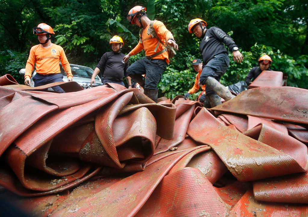 . Rescue personnel arrange large hoses and additional water pumps to continue a search operation for a young soccer team and their coach in a large flooded cave, Thursday, June 28, 2018, in Mae Sai, Chiang Rai province, in northern Thailand. A U.S. military team and British cave experts joined the rescue effort for 12 boys and their soccer coach missing for five days inside the cave being flooded by near-constant rains. (AP Photo/Sakchai Lalit)