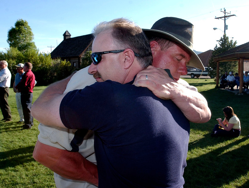 . Casey Farrell, right, owner of Gambles of Granby, hardware store that was demolished in Friday\'s rampage, hugs and thanks Grand County Undersheriff, Glen Trainor, during  a healing service held at Polhamus Municipal Park in Granby, June 7, 2004.  About 100 Granby residents  gathered at the park for prayer and an opportunity to share thoughts  about Friday\'s rampage through town which  resident, Marvin Heemeyer, drove a fortified bulldozer through town demolishing many buildings  and  ended up killing himself. (ANDY CROSS/THE DENVER POST)