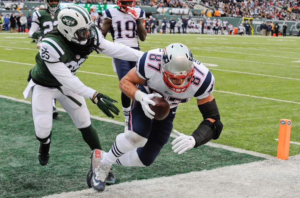 . New England Patriots tight end Rob Gronkowski (87) scores a touchdown as New York Jets\' Calvin Pryor (25) tackles him during the first half of an NFL football game Sunday, Dec. 21, 2014, in East Rutherford, N.J. (AP Photo/Bill Kostroun)