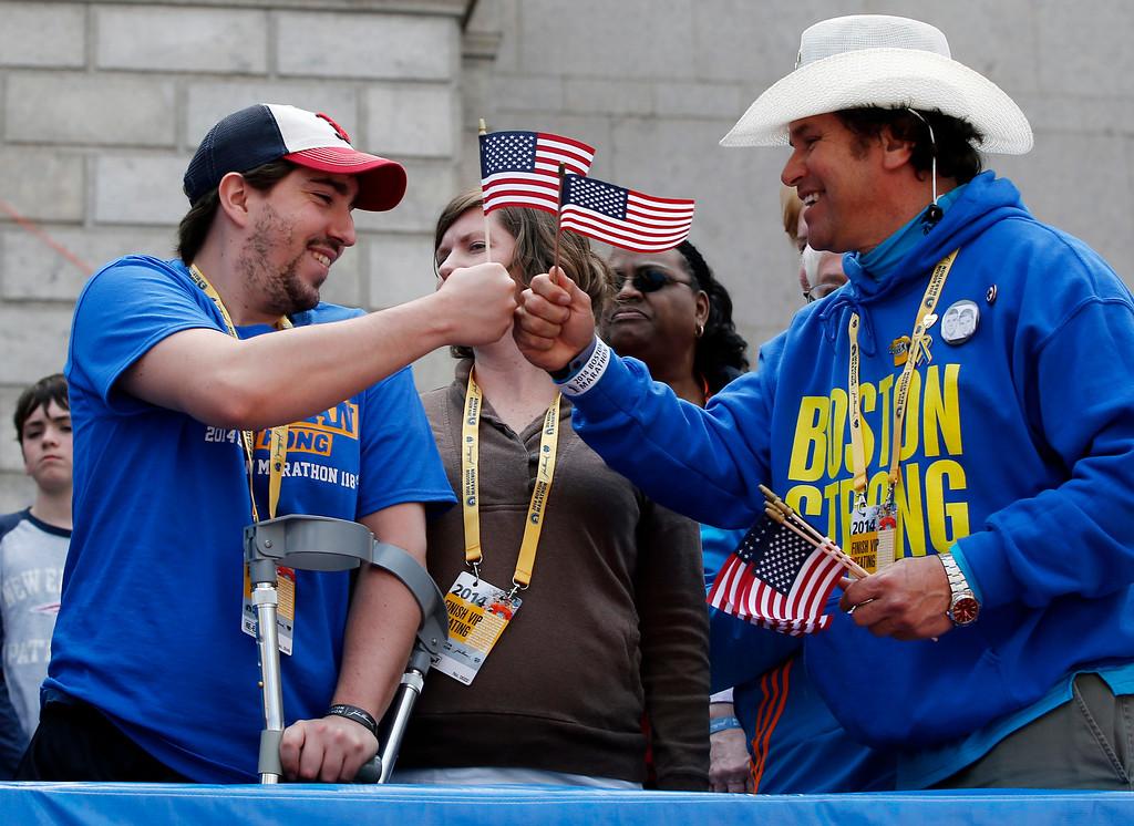 . Holding American flags, Boston Marathon bombing survivor Jeff Bauman, left, bumps fists with Carlos Arredondo near the finish line of the the 118th Boston Marathon, Monday, April 21, 2014, in Boston. (AP Photo/Elise Amendola, File)
