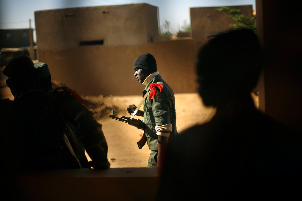 Description of . A Malian soldier walks in Gao, northern Mali, Thursday, Feb. 7, 2013. French troops began to withdraw from Timbuktu Thursday after securing the fabled city as they ramped up their mission in another northern Mali city, searching for Islamic extremists who may be mixing among the local population. (AP Photo/Jerome Delay)