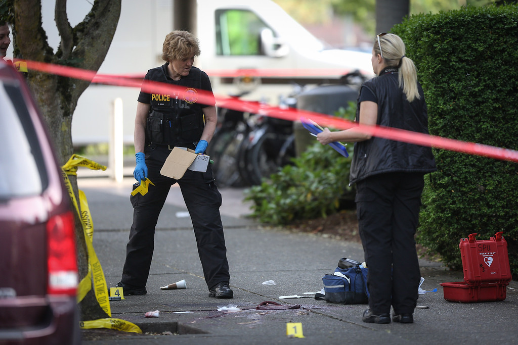 . Seattle police investigate the scene after a shooting at Seattle Pacific University on Thursday, June 5, 2014, in Seattle. A lone gunman armed with a shotgun opened fire  in a building at the small Seattle university, fatally wounding one person and injuring three others before a student subdued him with pepper spray as he tried to reload, Seattle police said. (AP Photo/seattlepi.com, Joshua Trujillo)