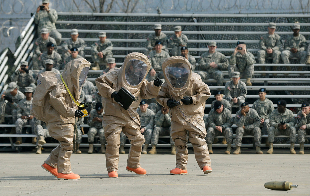 """. Soldiers of the U.S. Army 23rd chemical battalion, wearing anti-chemical suits, talk to each other near a mock bomb during a demonstration of their equipment at a ceremony to recognize the battalion\'s official return to the 2nd Infantry Division based in South Korea at Camp Stanley in Uijeongbu, north of Seoul, Thursday, April 4, 2013. The 23rd chemical battalion left South Korea in 2004 and returned with some 350 soldiers in Jan. 2013. The battalion will provide nuclear, biological and chemical detection, equipment decontamination and consequence management assistance to support the U.S. and South Korean military forces. North Korea warned Thursday that its military has been cleared to attack the U.S. using \""""smaller, lighter and diversified\"""" nuclear weapons, while the U.S. said it will strengthen regional protection by deploying a missile defense system to Guam. (AP Photo/Lee Jin-man)"""