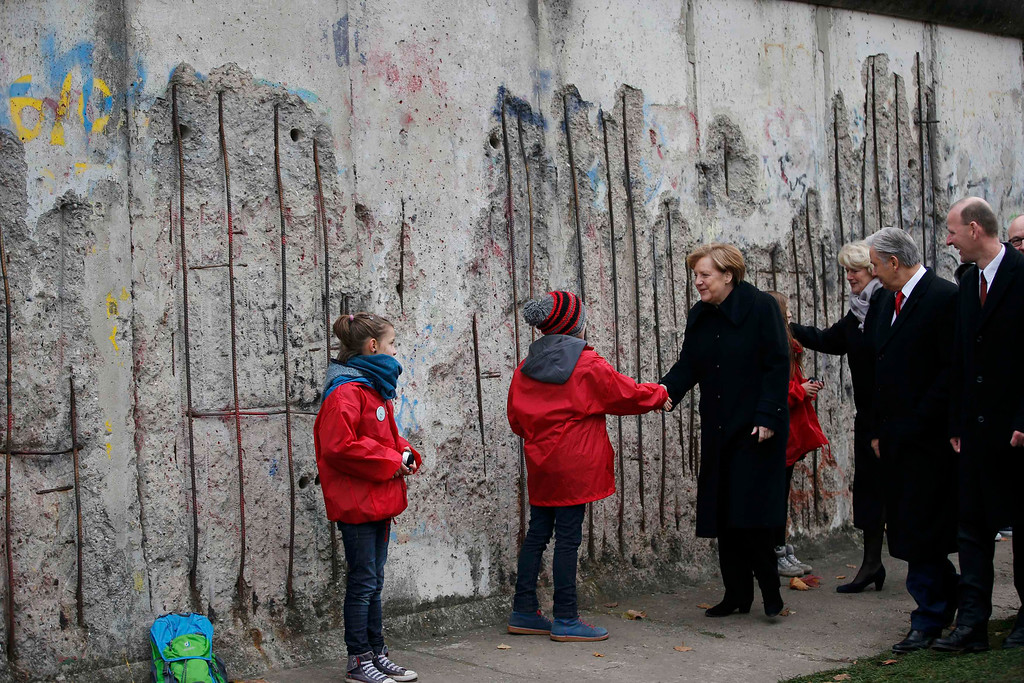 . German Chancellor Angela Merkel, Berlin Mayor Klaus Wowereit and Director of the Berlin Wall Foundation Axel Klausmeier, from left,shake hands with children symbolizing the so-called \'Mauerspechte\' (\'wall peckers\', people who chipped the wall with hammers) at a memorial in Bernauer Strasse in Berlin, Germany, Sunday, Nov. 9, 2014. 25 years ago - on Nov. 9, 1989 - the East-German government lifted travel restrictions and thousands of East Berliners had pushed their way past perplexed border guards to celebrate freedom with their brethren in the West. (AP Photo/Fabrizio Bensch, Pool)