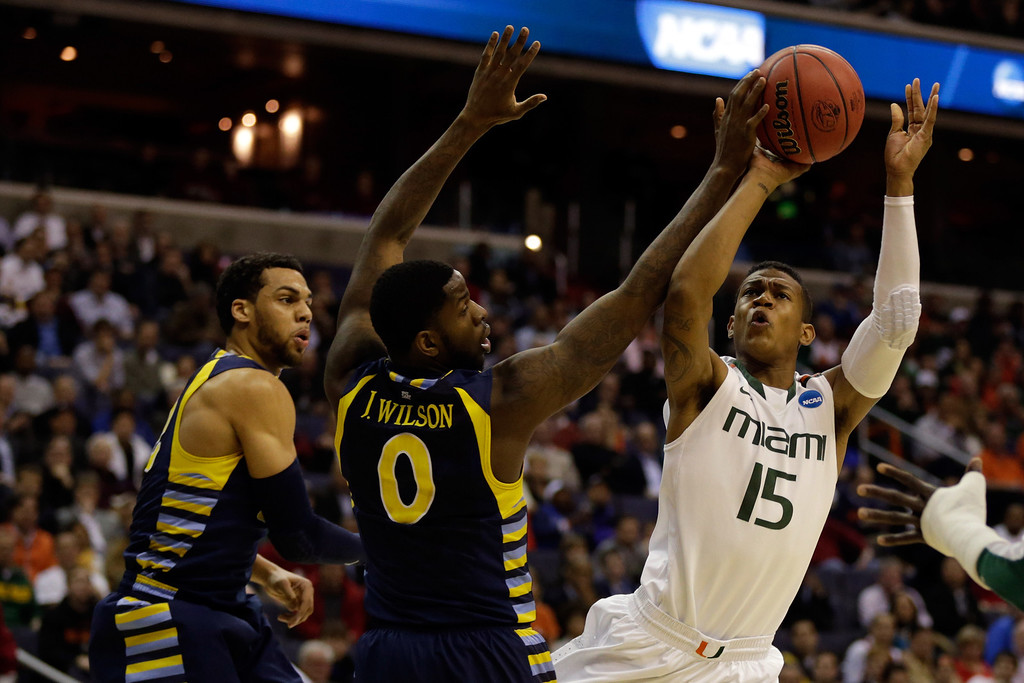 . WASHINGTON, DC - MARCH 28:  Rion Brown #15 of the Miami (Fl) Hurricanes goes to the hoop against Jamil Wilson #0 and Trent Lockett #22 of the Marquette Golden Eagles during the East Regional Round of the 2013 NCAA Men\'s Basketball Tournament at Verizon Center on March 28, 2013 in Washington, DC.  (Photo by Win McNamee/Getty Images)