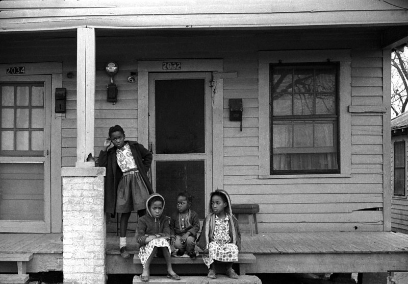 Children standing and seated on steps of porch while looking at marchers