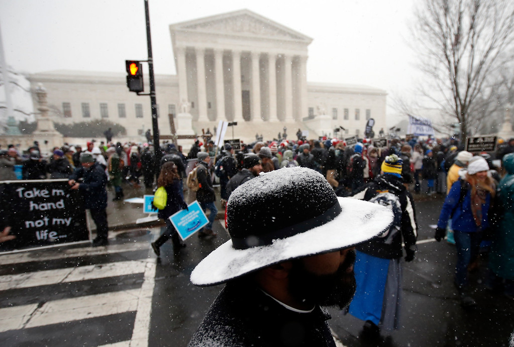 . Snow covers the hat of Father Jack Soler of the New York borough of Staten Island during the March for Life 2016, in front of the U.S. Supreme Court,  Friday, Jan. 22, 2016 in Washington, during the annual rally on the anniversary of 1973 \'Roe v. Wade\' U.S. Supreme Court decision legalizing abortion. (AP Photo/Alex Brandon)