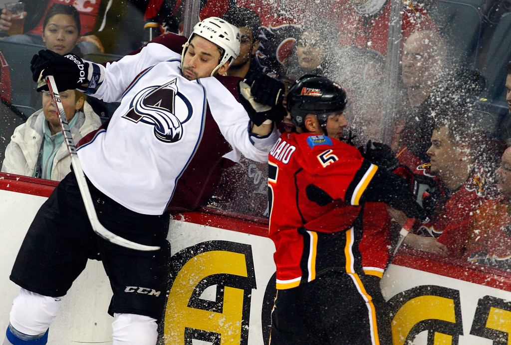 . Colorado Avalanche\'s Patrick Bordeleau, left, crashes into the boards after chasing Calgary Flames\' Mark Giordano during the second period of an NHL hockey game Thursday, Jan. 31, 2013, in Calgary, Alberta. (AP Photo/The Canadian Press, Jeff McIntosh)