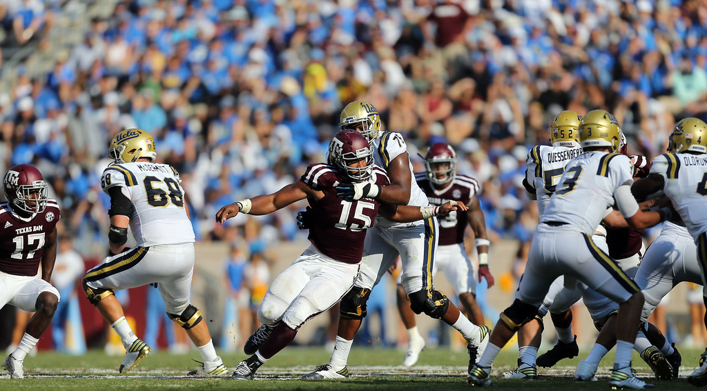 . Texas A&M defensive lineman Myles Garrett (15) fights his way around UCLA offensive lineman Kenny Lacy (76) during the fourth quarter of an NCAA college football game against Saturday, Sept. 3, 2016, in College Station, Texas. Texas A&M won 31-24 in overtime. (AP Photo/Sam Craft)