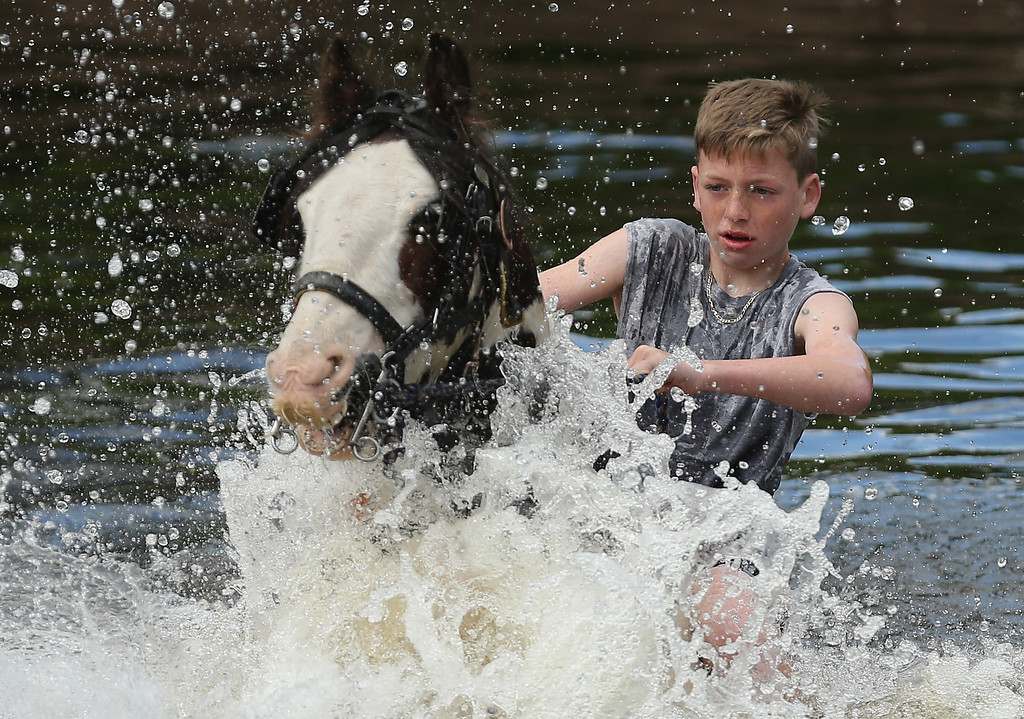 . Young traveller Leonard (no surname gven) washes his horse Shy Boy in the River Eden during the Appleby Horse Fair on June 4, 2015 in Appleby, England. The Appleby Horse Fair has existed under the protection of a charter granted by James II since 1685 and is one of the key gathering points for the Romany, gypsy and traveling community. The fair is attended by about 5,000 travelers who come to buy and sell horses. The animals are washed and groomed before being ridden at high speed along the \'mad mile\' for the viewing of potential buyers.  (Photo by Christopher Furlong/Getty Images)