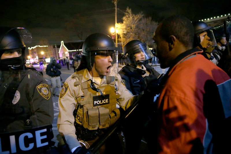 . Police officers confront protesters after the announcement of the grand jury decision not to indict police officer Darren Wilson in the fatal shooting of Michael Brown, an unarmed black 18-year-old, Monday, Nov. 24, 2014, in Ferguson, Mo. (AP Photo/David Goldman)