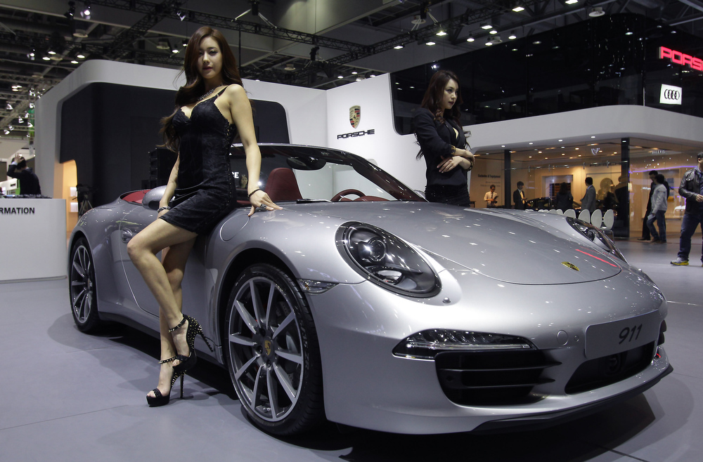 . Models pose next to a Porsche 911 at the Seoul Motor Show 2013 on March 28, 2013 in Goyang, South Korea. The Seoul Motor Show 2013 will be held in March 29-April 7, featuring state-of-the-art technologies and concept cars from global automakers. The show is its ninth since the first one was held in 1995. About 384 companies from 14 countries, including auto parts manufacturers and tire makers, will set up booths to showcase trends in their respective industries, and to promote their latest products during the show.  (Photo by Chung Sung-Jun/Getty Images)