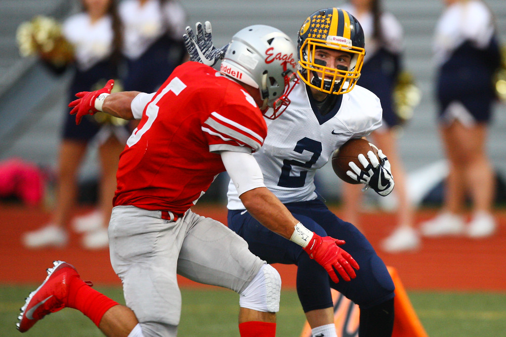 . David Turben - The News-Herald Kirtland\'s Jake Neibecker (2) tries to cut back on Geneva\'s Blake Peet (5).