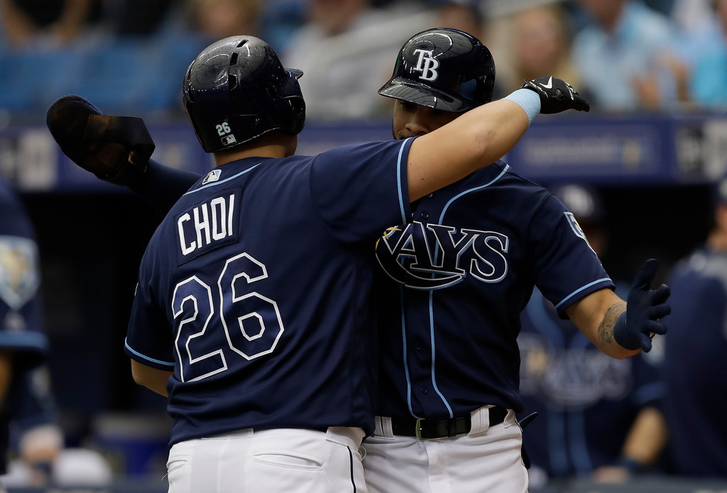 . Tampa Bay Rays\' Ji-Man Choi, of South Korea, (26) hugs Tommy Pham after Choi hit a two-run home run off Cleveland Indians pitcher Carlos Carrasco during the first inning of a baseball game Wednesday, Sept. 12, 2018, in St. Petersburg, Fla. (AP Photo/Chris O\'Meara)