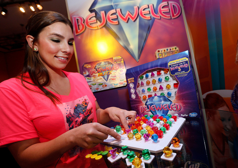 . Game demonstrator Aubree Marchione matches colored gems in Hasbroís new BEJEWELED Game in the companyís showroom at the American International Toy Fair, Monday, Feb. 11, 2013, in New York. (Photo by Jason DeCrow/Invision for Hasbro/AP Images)