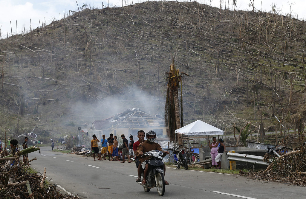 . A hill of uprooted coconut trees is seen in the background as Filipino men on a motorcycle go past residents of a typhoon-affected community in Eastern Samar Province, Philippines, 21 November 2013.  EPA/ROLEX DELA PENA