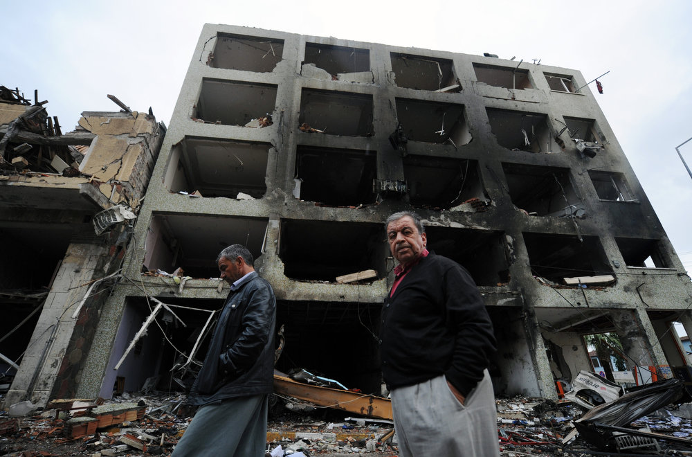 . People pass by one of the Saturday explosion sites that killed 46 and injured about 50 others, in Reyhanli, near Turkey\'s border with Syria, Sunday, May 12, 2013.  The bombings on Saturday marked the biggest incident of cross-border violence since the start of Syria\'s bloody civil war and has the raised fear of Turkey being pulled deeper into the conflict. (AP Photo)