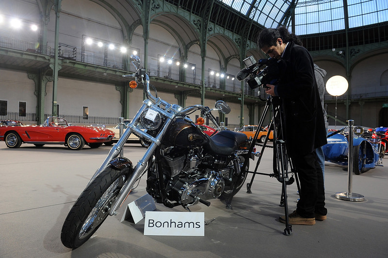. A reporter films the 2013 Harley Davidson 1 585 cm3 Dyna Super Glide Custom, donated to Pope Francis last year and signed by him on its tank, ahead of Bonham\'s sale of vintage cars, at Le Grand Palais on February 5, 2014 in Paris, France.  (Photo by Antoine Antoniol/Getty Images)